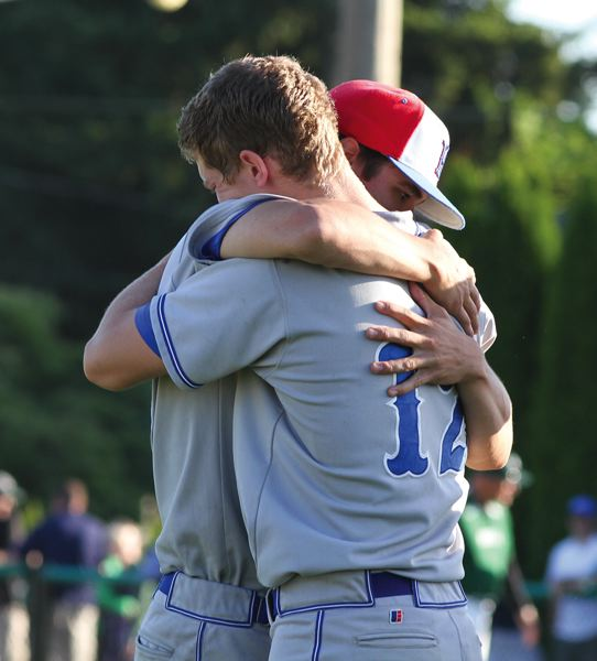 by: HILLSBORO TRIBUNE PHOTO: AMANDA MILES - Hillsboro senior Chase Kaplan (12) gets a hug from a teammate after Tuesday's playoff loss to Sheldon.