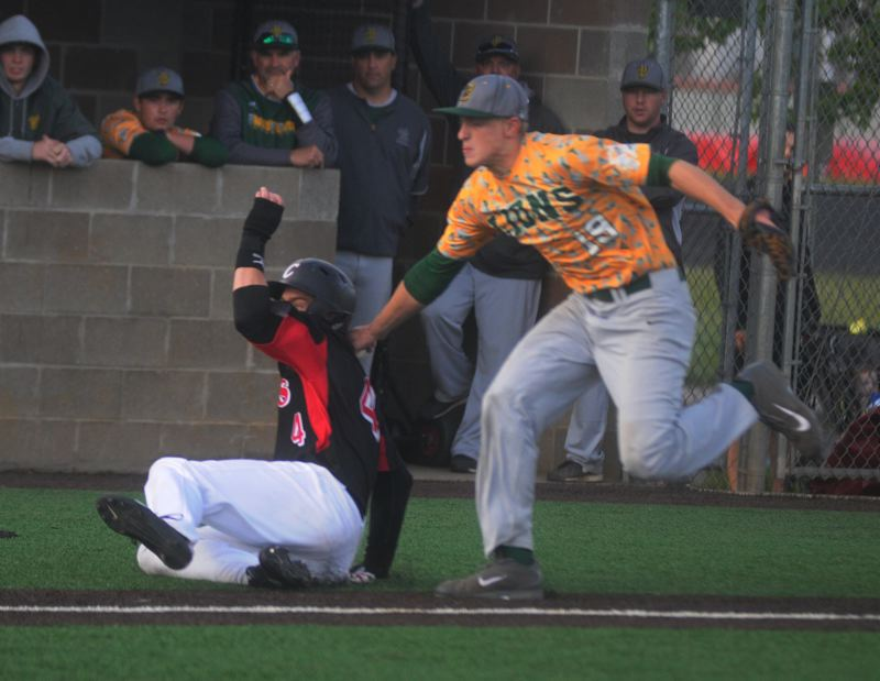 by: MATTHEW SHERMAN - West Linn's Karsen Lindell applies a tag on a Clackamas runner down the third-base line in the Lions' playoff game with Clackamas last week.