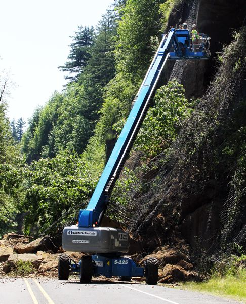by: OUTLOOK PHOTO: CARI HACHMANN - Crews scope the rock face to make sure it is safe for workers to begin clearing debris.