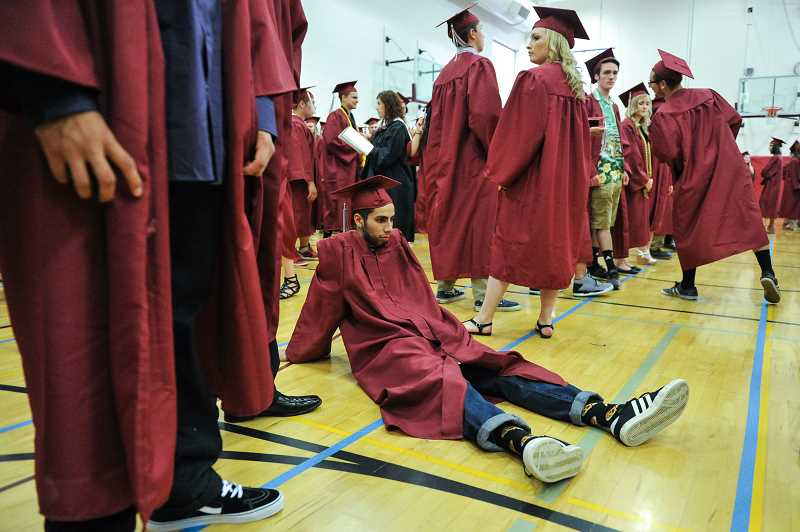 by: GAZETTE PHOTO: JOHN LARIVIERE - Victor Polanco relaxes as the Sherwood graduates assemble in preparation of the 2014 commencement ceremony.
