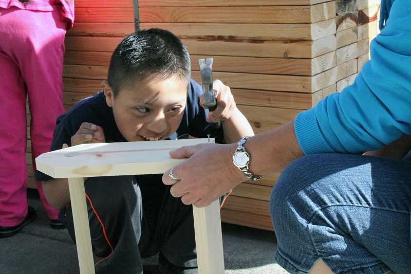by: TYLER FRANCKE | WOODBURN INDEPENDENT - Ishmael Avendano-Lopez hammers a nail during his Life Skills class's field trip to Long Bros. Building Supply in Woodburn.