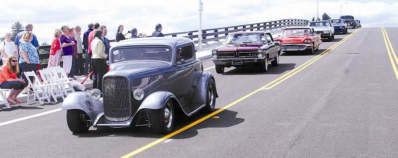 by: RAY HUGHEY - A line of classic cars travels over the newly completed bridge on Sequoia Parkway.