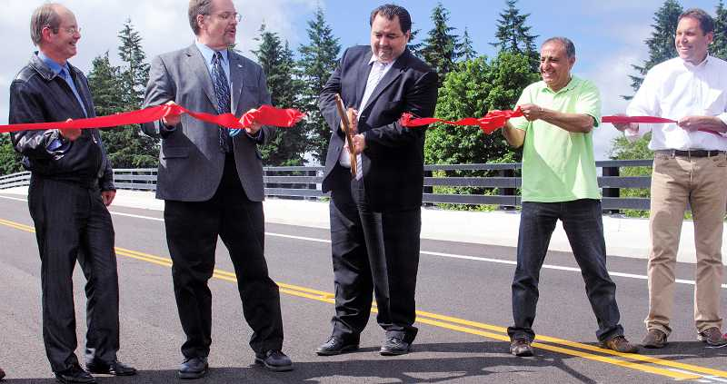 by: RAY HUGHEY - Canby Mayor Brian Hodson (with scissors) officially opens the new section of Sequoia Parkway Monday.
