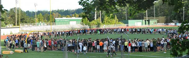 by: TIDINGS PHOTO: VERN UYETAKE - Students, parents, teachers and community members gathered at the West Linn High School football field Monday night for a vigil.