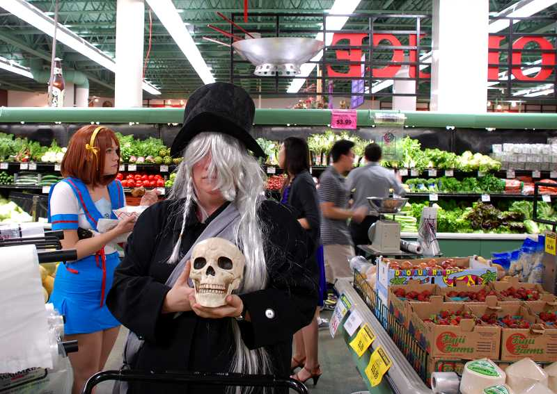 by: TIMES PHOTO: KEITH SHEFFIELD - Heidi Chairet, of Canby, poses as the 'Black Butler' in Uwajimaya's produce section. Her friend Steffany Hansen, of Oregon City, dressed as 'Haruhi.'