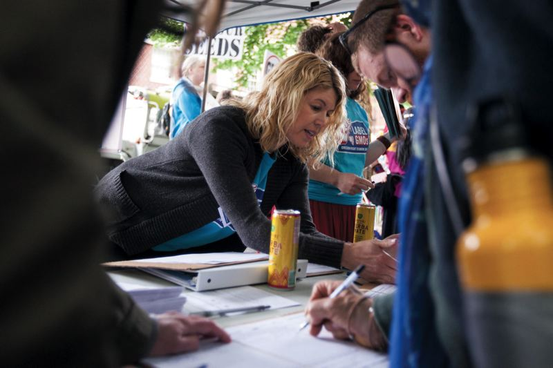 by: SPECIAL TO PAMPLIN MEDIA GROUP: JEFFREY BALL - Dahviya Davis, a volunteer with Right To Know Oregon, collects petition signatures for a state ballot initiative that would require labeling of foods containing genetically modified organisms.