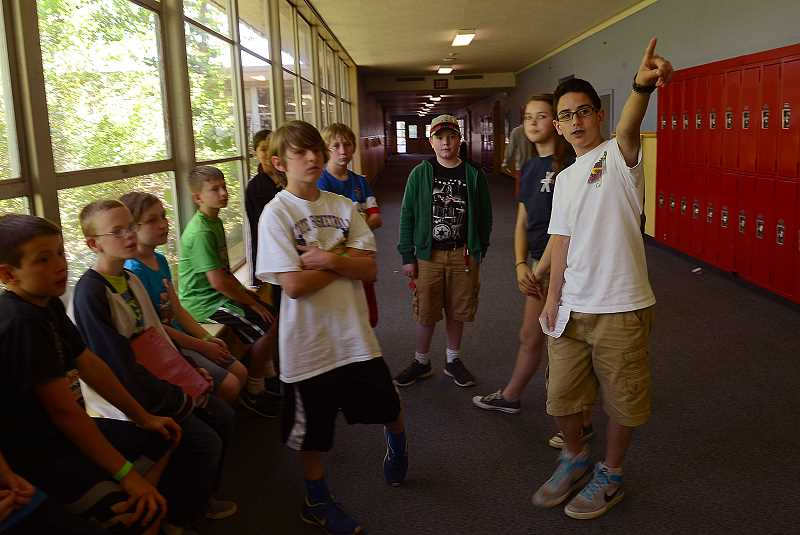 by: REVIEW PHOTO: VERN UYETAKE - Jake Ferdig, right, leads a group of fifth-graders on a tour of Lake Oswego Junior High.