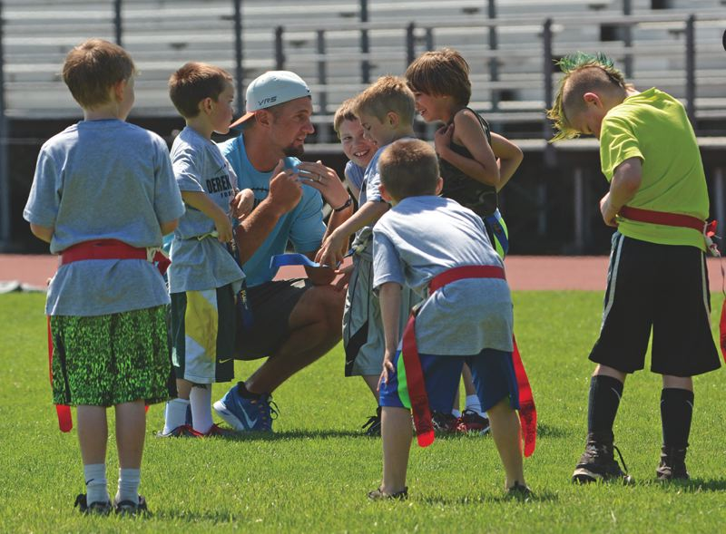by: JOHN WILLIAM HOWARD - Derek Anderson, former Scappoose High School and Oregon State University quarterback, gathers the 'blue team' around him and prepares a play during the annual Derek Anderson Football Camp on June 7. Anderson, now playing for the Carolina Panthers of the NFL, said it's a great chance for the young kids to learn about football, and if nothing else, have an absolute blast.