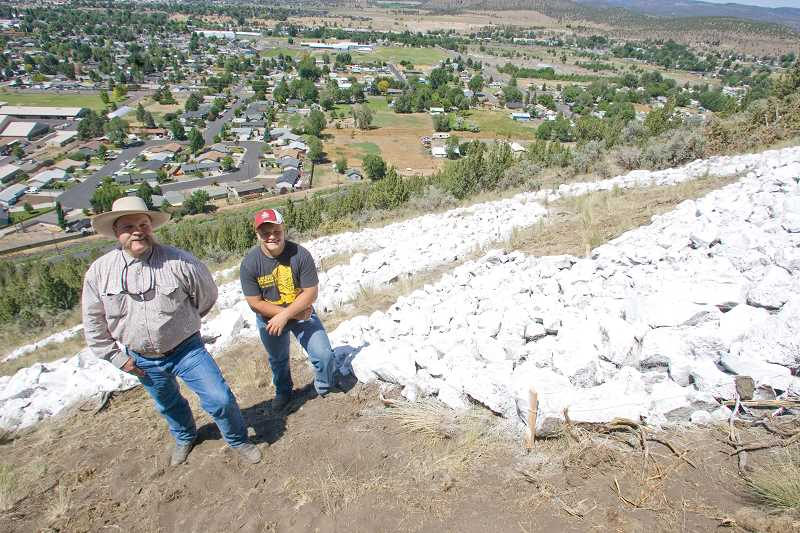 by: KEVIN SPERL - Wyatt Moss (right) stands with his dad, Hank, at the site of their renovated 'CC' sign on the hill overlooking Prineville.