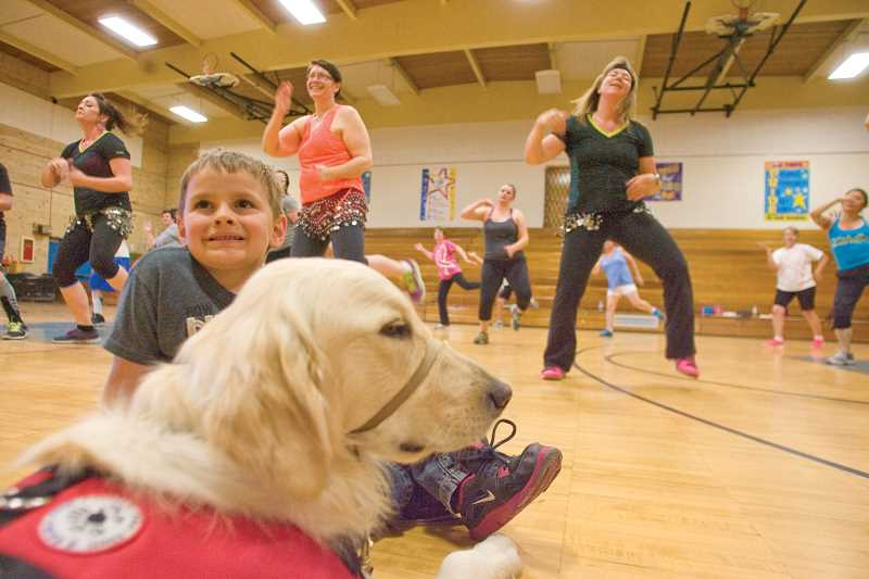 by: KEVIN SPERL - Stryder Doescher and his alert dog, Keebler, hang out in the Cecil Sly gym during Monday night's Zumba fundraiser to support Stryder's upcoming surgical procedures.