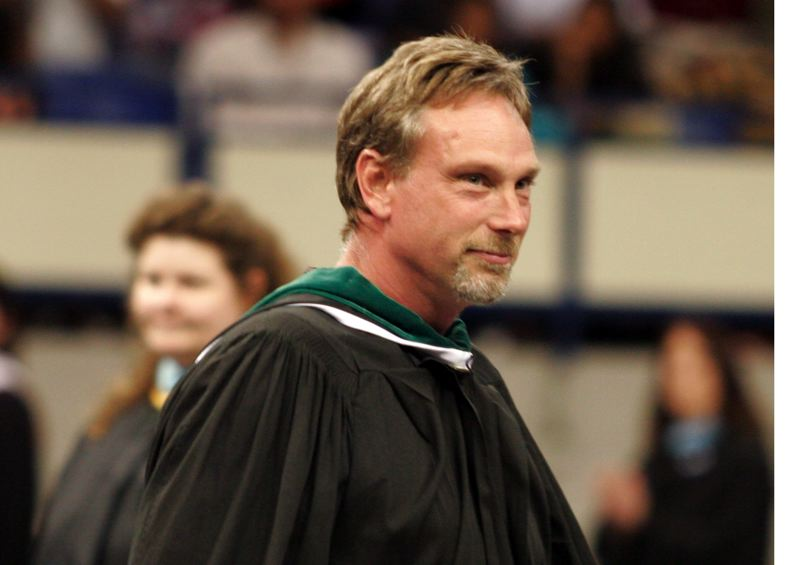 by: OUTLOOK PHOTO: JIM CLARK - Reynolds High School teacher Todd Rispler was cheered when he walked onto the floor at the beginning of graduation. On the morning of the shooting, Rispler, grazed by a bullet on his hip, made his way to the office, where he was able to notify the administration, which then initiated an immediate lockdown probably saving many lives.