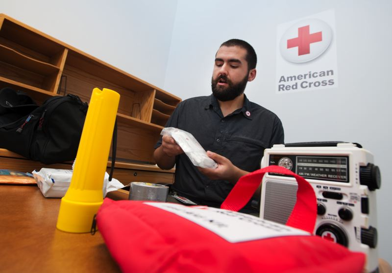 by: TRIBUNE PHOTO: JOHN M. VINCENT - Willie Bence, American Red Cross Disaster Program Manager for West Metro Portland, shows an emergency starter kit. Preparing employees with such kits may mean the difference between them coming to work or not.