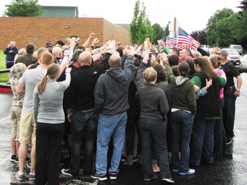 by: OUTLOOK PHOTO: ANNE ENDICOTT - Reynolds teachers share a group cheer, shouting 'Raiders,' after installing the flags.