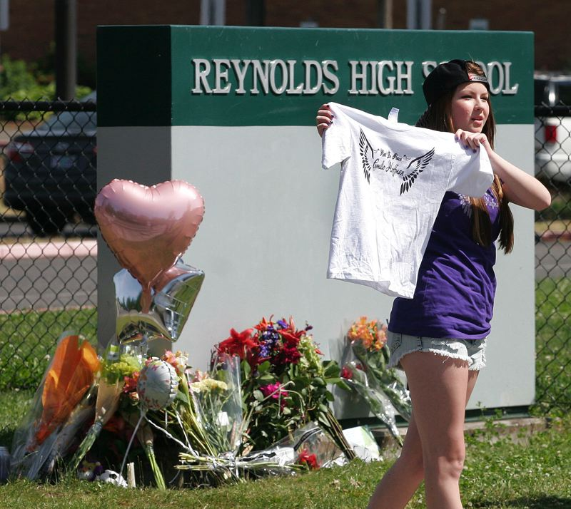 by: OUTLOOK PHOTO: JIM CLARK - Alexie Malone, a freshman at Reynolds High School, holds up a T-shirt that she was giving away to people who arrived Wednesday at a makeshift memorial outside Reynolds High School.