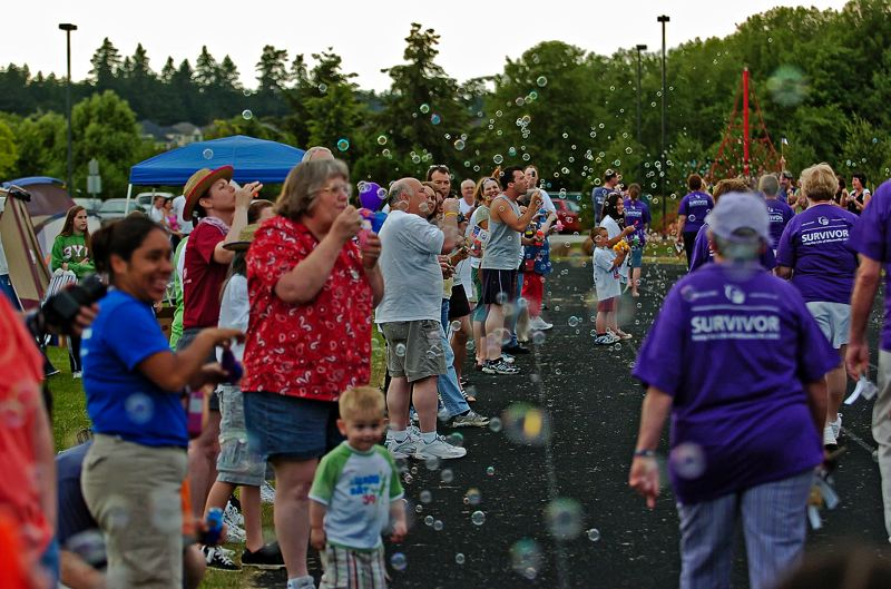 by: SUBMITTED PHOTO - Cancer survivors take part in the ceremonial survivors walk at an earlier Relay event at Wood Middle School in Wilsonville.