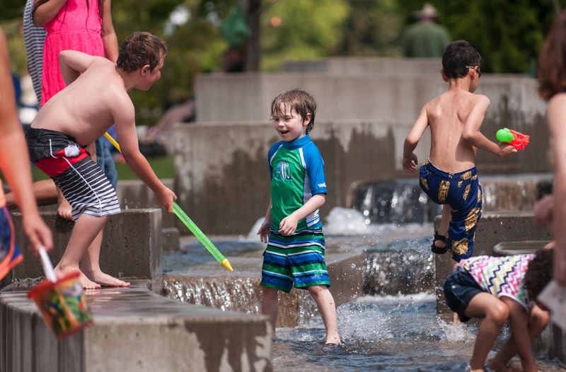 by: SPOKESMAN PHOTO: JOSH KULLA - Daniel Hickson (center), 6, enjoys the Town Center Park water feature during this years Wilsonville Festival of Arts.