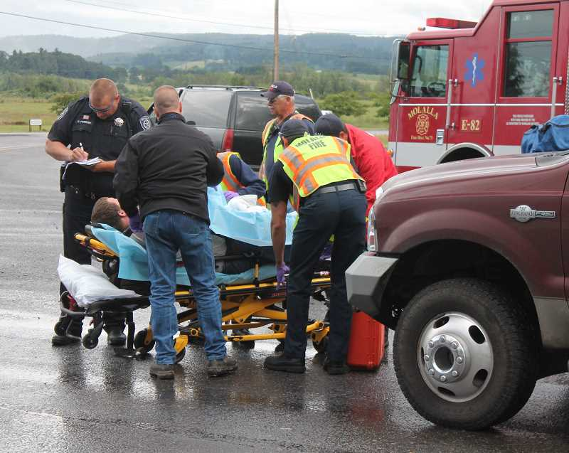by: JIM BESEDA/MOLALLA PIONEER - Emergency personnel assist the driver of a Ford Focus ZX3 that collided with a Chevrolet pick-up truck at the Y-intersection near the east end of Main Street in Molalla about 5:10 p.m. Monday.