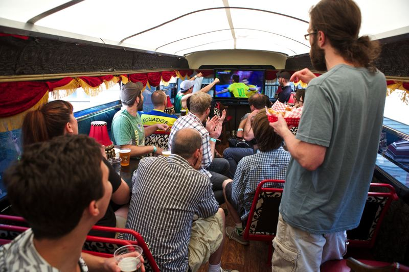 by: TRIBUNE PHOTO: JAIME VALDEZ - Soccer fans celebrate Wednesday after Brazil scored a goal against Croatia in a double-decker bus in the Bus Stop Cafe at the World Cup Beer Garden on Northwest 21st Avenue. Portlanders are gathering at all hours to watch the matches across Soccer City USA.