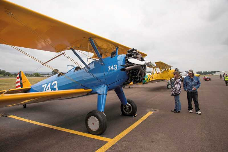 Rick and Tracey Poublon, of Oregon City, admire the vintage airplalnes on display at the Warbirds of the West event at the Aurora State Airport.