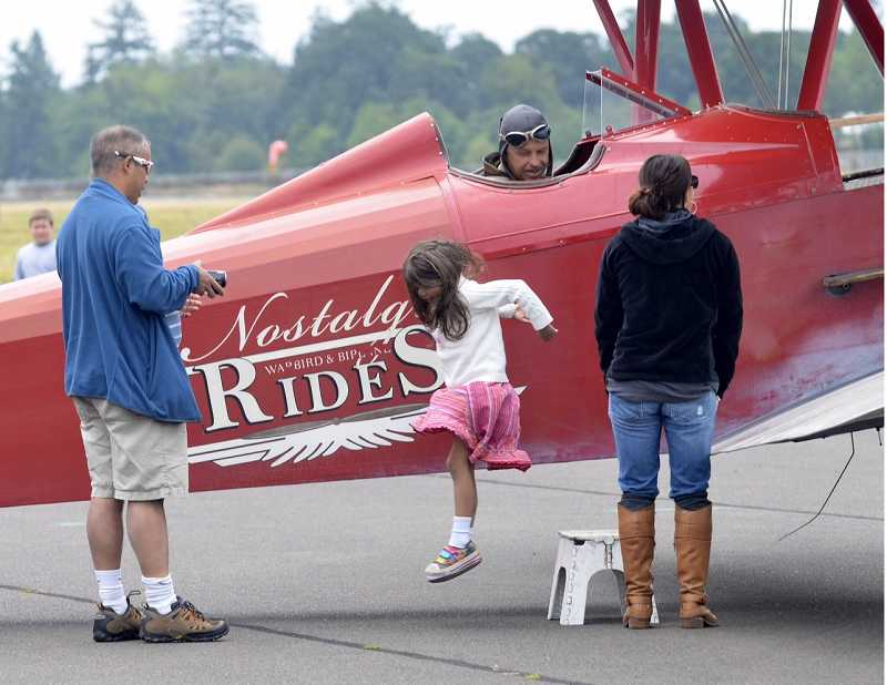 Inara Kerketta, of Tigard, center, hops down after she and her father, Amrik Kerketta, left, return from a bi-plane ride Saturday at the Warbirds of the West air show. 'It was fantastic,' her father said. 'It was windy but fun. It's incredible to see everything from an open cockpit. It was noisy and windy and her hair was flying all over the place, but she loved it.