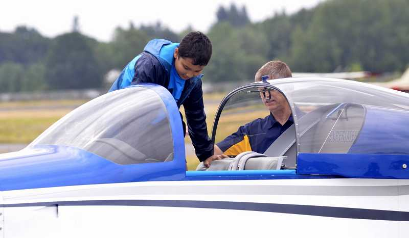 Callon Keo, 9, of Wilsonville, gets some help from Mark Cattell, of the Experimental Aircraft Association, for his first airplane ride.