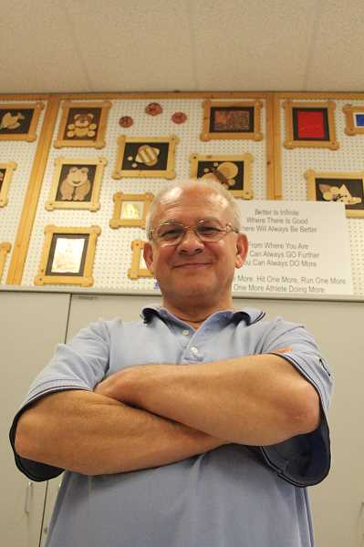 by: LINDSAY KEEFER - Steve Laue, who's retiring from teaching after 40 years, poses in front of a wall of student artwork completed in his class.