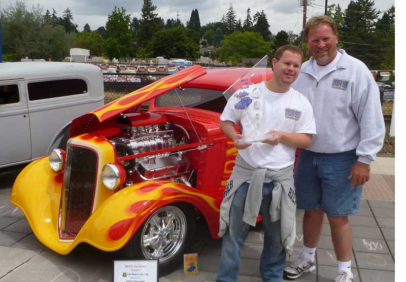 by: COURTESY OF SIERRA DONAHUE  -  Best of Show winner Gene Baxter poses with his son, Mat, in front of their 1934 Chevrolet 3 Window Coupe.