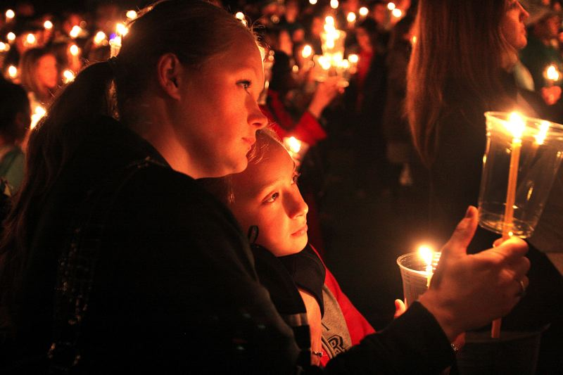 by: OUTLOOK PHOTO: JIM CLARK - Karri Miller, left, and her daughter Emiley Bradley hold candles at the candlelight vigil held Tuesday night at Reynolds High School. The community came to show their grief for the loss both students, the victim, Emilio Hoffman and the shooter, Jared Padgett.