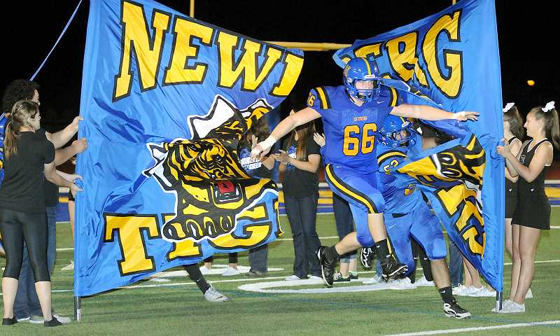 by: GARY ALLEN - Breakout season - Lineman Dakota Church busts through a banner during the Tigers 2013 season, for which the Newberg native earned honorable mention all-state as a defensive lineman.