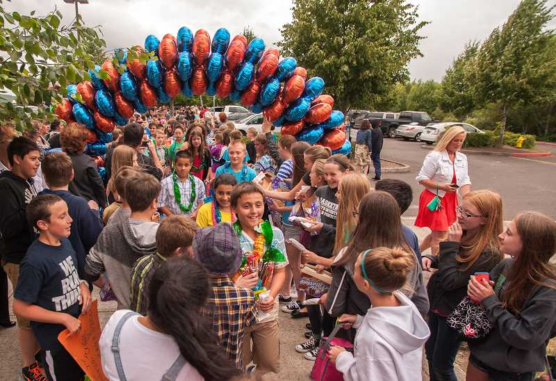 by: SPOKESMAN PHOTO: JOSH KULLA - It's a chaotic scene under the archway as Boones Ferry fifth-graders, including Langdon Ling (facing camera, front) are greeted by Wood Middle School ambassadors, teachers and parents.