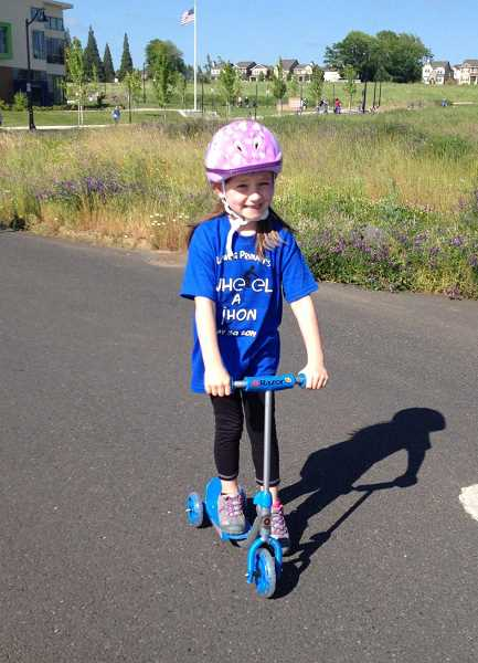 by: SUBMITTED PHOTO - Wearing her official Wheel-a-thon T-shirt, Claire Keith is all smiles as she mounts her scooter for the schools second-annual event May 30.