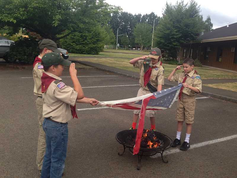 by: SUBMITTED PHOTO - From left to right, Boy Scouts Noah Heidelberger, Logan Carpenter, Kairon Smith and Carter Troha take part in a flag retirement ceremony June 14.