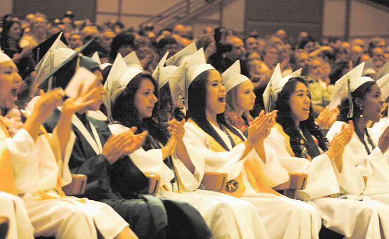 by: PHIL HAWKINS - Members of North Marion's graduating class applaud a speech during graduation ceremonies June 6 at Rolling Hills Community Church in Tualatin.