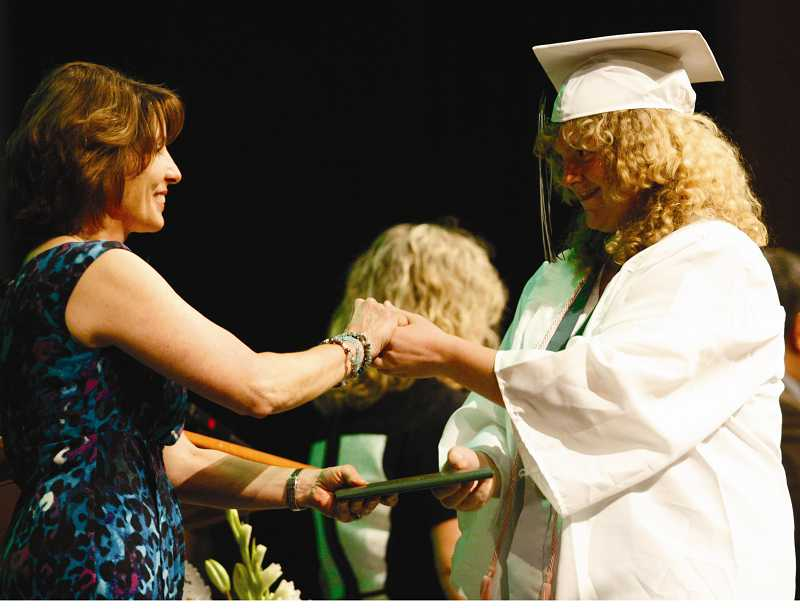 by: PHIL HAWKINS - Stacy Caldwell accepts her diploma from June Miller, chairwoman of the North Marion School Board.
