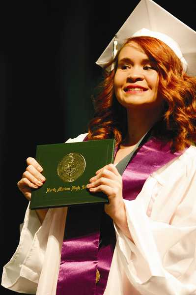 by: PHIL HAWKINS - Bekah Dron shows off her diploma