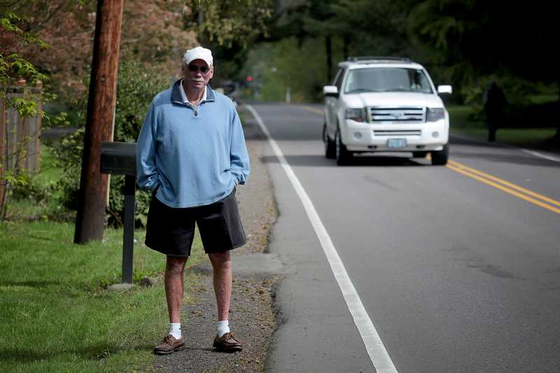 by: TIMES PHOTO: JONATHAN HOUSE - John Farmer stands on Laurelwood Avenue, where there are no sidewalks. A fatal accident last year led him to take pledges from neighbors in the hope of putting in speed bumps.