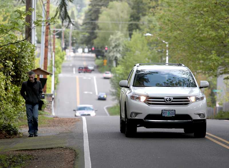 by: TIMES PHOTO: JONATHAN HOUSE - A pedestrian is forced to walk on a driveway along Laurelwood Avenue due to a lack of sidewalks in the neighborhood.