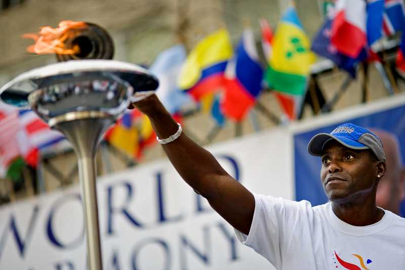 Olympian Carl Lewis lights the flame at the run's opening ceremony in New York.