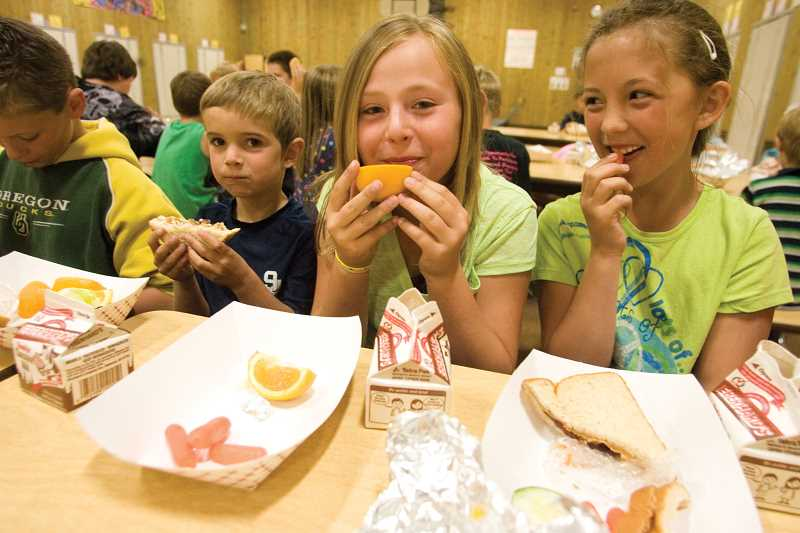 by: KEVIN SPERL/CENTRAL OREGONIAN - Brooke Everest (right), Bailey Everest, Max LeFevre and Darrah Johnson eat lunch at the Crook County Kids Club at Cecil Sly on Wednesday. Lunch for those attending is provided as part of the summer free meal program.