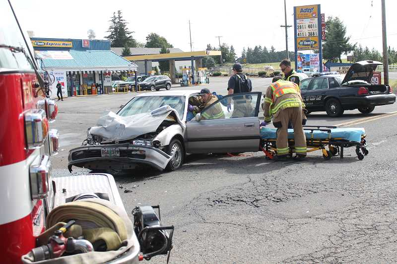 by: JIM BESEDA/MOLALLA PIONEER - Emergency personal from the Molalla Rural Fire District No. 73 and the Molalla Police Department assist a female driver after her car crashed into a pick-up truck at the Y-intersection at the east end of Main Street Friday morning.