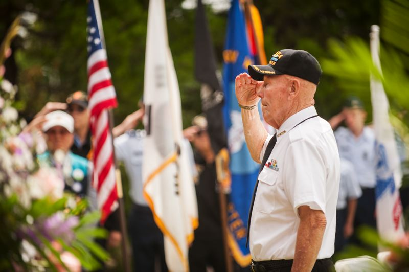 by: SPOKESMAN PHOTO: JOSH KULLA - Korean War veteran Richard 'Dick' DeMers salutes the floral wreaths displayed at Wilsonville's Korean War Memorial at a June 21 commemoration of the war's beginning.