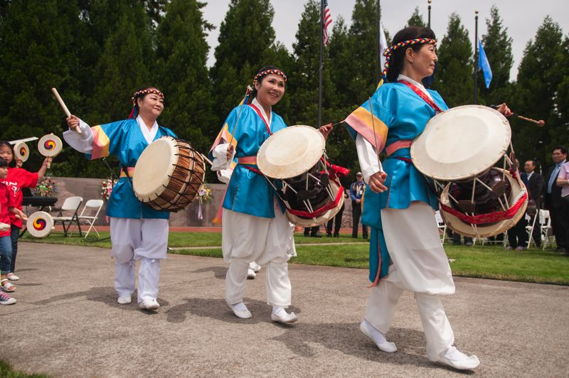 by: SPOKESMAN PHOTO: JOSH KULLA - Members of the Oregon Korean Culture Art Center's drum group performed June 21 at Wilsonville's Town Center Park as part of a commemoration of the beginning of the Korean War.