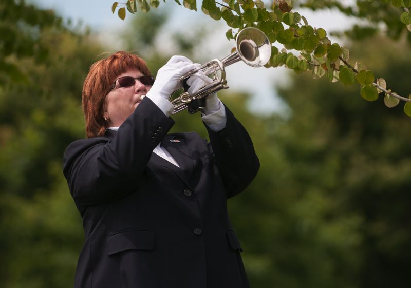 by: SPOKESMAN PHOTO: JOSH KULLA - Wilsonville resident Sue Lamb plays taps June 21 at a Korean War commemoration ceremony at Wilsonville's Town Center Park.