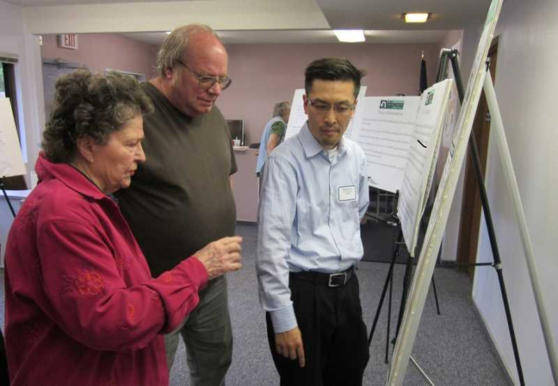by: BARBARA SHERMAN - GETTING THE SCOOP - David Kim (right), ODOT area manager, answers questions about the 99W project from Billie Reynolds of King City and Doug Dunster of Royal Villas, who said he opposes the project in part because Royal Villas residents will no longer be able to turn south on 99W but have to drive north to Durham Road and made a U-turn.