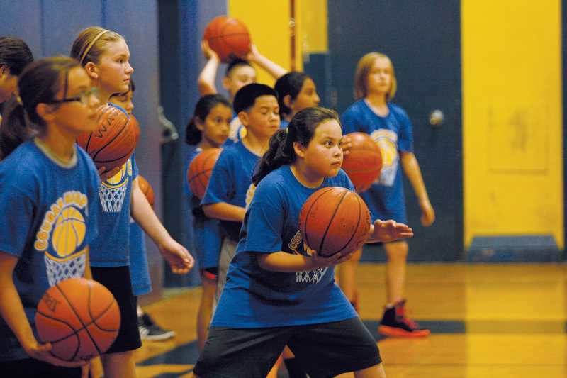 by: PHIL HAWKINS - Members of the Gervais basketball camp line up in preparation for dribbling drills.