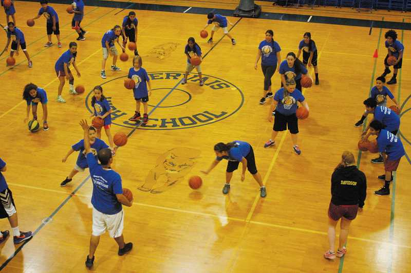 by: PHIL HAWKINS - Gervais coach Kyle Buse conducts dribbling drills at the Cougar Hoop Camp, which attracted dozens of local athletes at the elementary and middle school levels. Buse was assisted by members of the Gervais girls varsity basketball team.