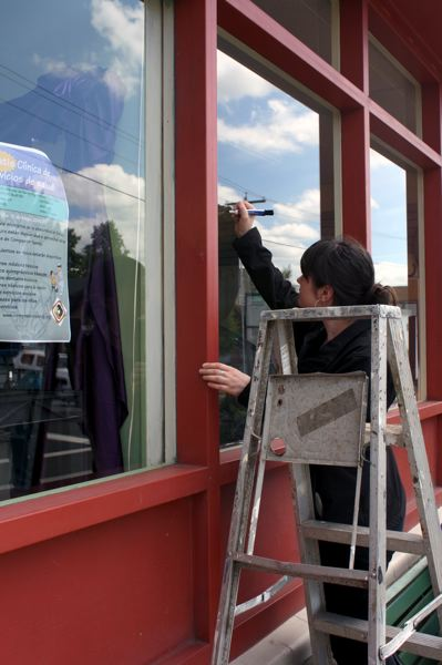 by: POST PHOTO: KYLIE WRAY - One volunteer is working to paint the Action Centers front windows to make them more inviting and express its mission centering on food.