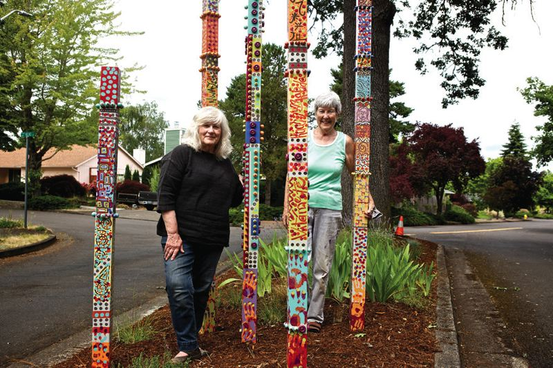 by: TIMES PHOTO: JAIME VALDEZ - Linda Ferreira and Wendy Kroger stand on a island on Southwest Settler Way where they and neighbors planted 'Welcome Totems' they created. The totems will be unveiled during the second-annual Greenway Garden Tour on Saturday at 10 a.m.