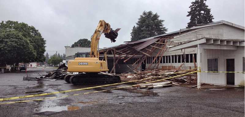 by: RAY HUGHEY - A cat goes about the task of tearing down the livestock building at the Clackamas County fairgrounds.