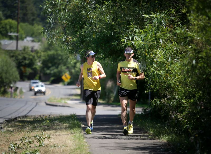 by: TIMES PHOTO: JONATHAN HOUSE - Jason Zacher, left, and running partner Dane Rauschenberg head down Cornell Road during Zachers 188-mile run to raise money for Operation School Bell, a Beaverton-based childrens charity.